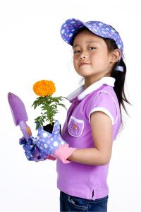 A little girl in gardening gloves holds a gardening tool and a flower