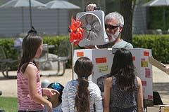 A man shows a science fair project to some youth